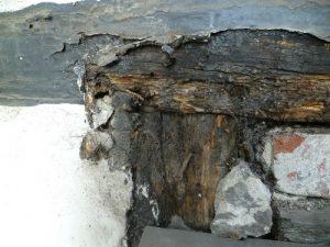 Beschädigter Holzbalken unter Beschichtung.